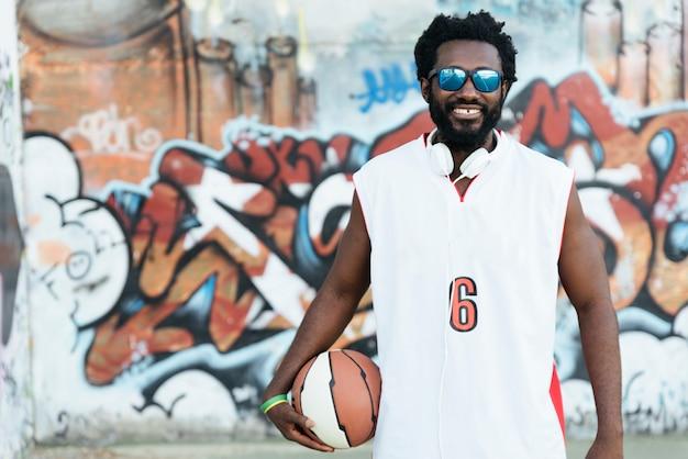 Portrait d'un homme noir avec des vêtements de sport décontractés et un ballon de basket.