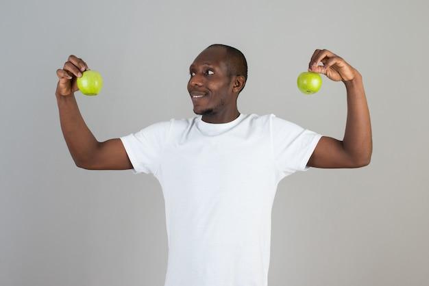 Portrait d'un homme à la peau foncée en t-shirt blanc regardant des pommes vertes sur un mur gris