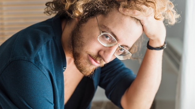 Portrait d'un homme pensant avec des lunettes