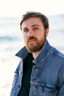 Portrait d'un homme pensif dans une veste en jean dans le contexte de la mer en gros plan