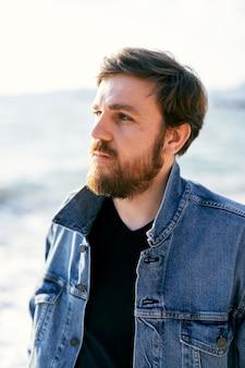 Portrait d'un homme pensif dans une veste en jean regardant au loin dans le contexte de la