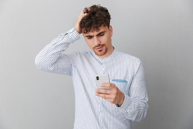 Portrait d'un homme perplexe brune vêtu d'une chemise saisissant sa tête tout en tenant et en utilisant un smartphone isolé sur un mur gris