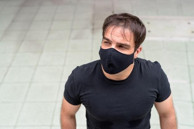 Portrait d'homme persan avec masque de protection contre l'épidémie de virus corona dans la ville