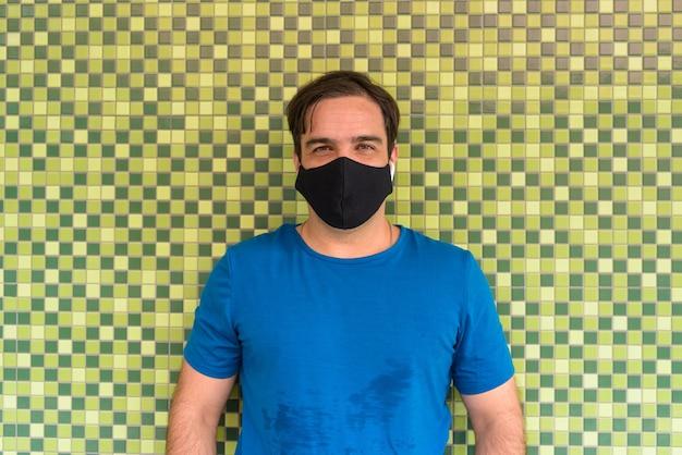Portrait d'homme persan avec masque de protection contre l'épidémie de virus corona sur vert