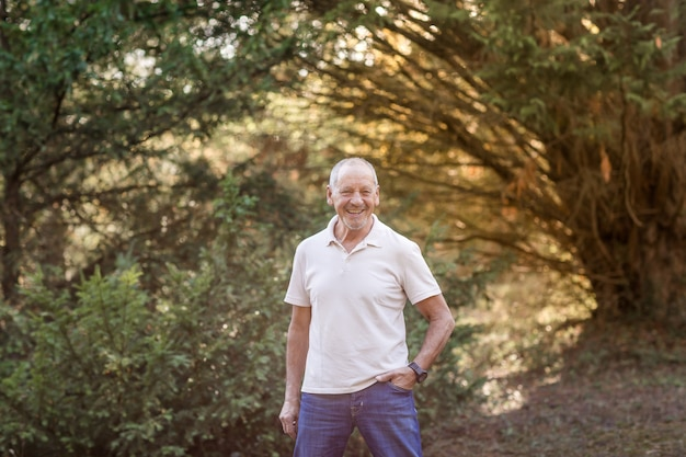 Portrait d'un homme plus âgé heureux et souriant, avec une main dans la poche de son pantalon en se promenant dans les bois parmi les arbres au coucher du soleil.