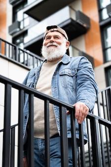 Portrait d'un homme plus âgé posant dans les escaliers à l'extérieur de la ville