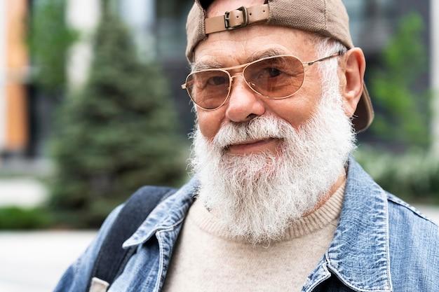 Portrait d'un homme plus âgé posant à l'extérieur de la ville
