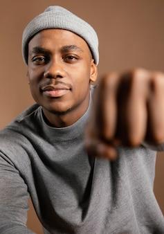 Portrait homme portant une casquette montrant le poing