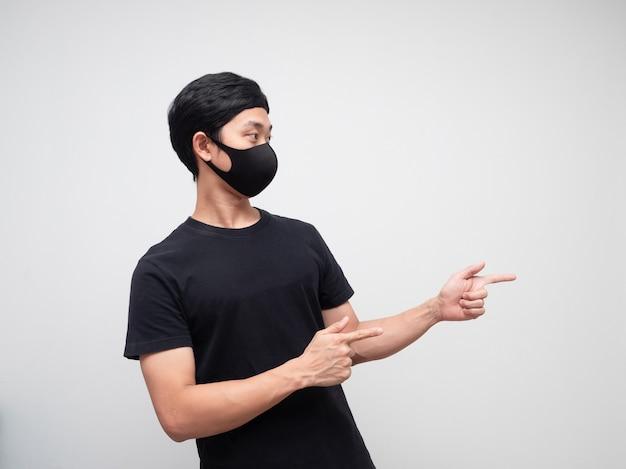 Portrait homme portant un masque double doigt pointé et regardant le côté droit sur fond blanc