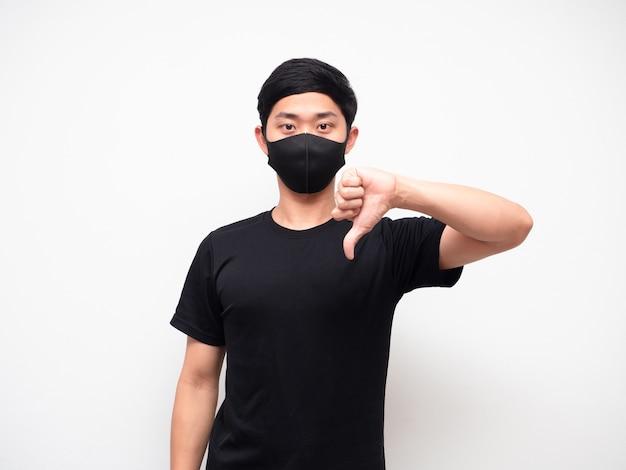 Portrait homme portant un masque montrer le pouce vers le bas en désaccord en regardant la caméra sur fond blanc