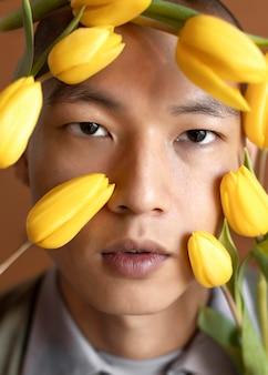 Portrait homme posant avec des fleurs