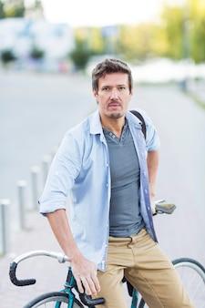 Portrait d'homme posant avec son vélo