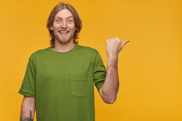 Portrait d'homme positif avec une coiffure blonde et une barbe. porter un t-shirt vert. a un tatouage. et pointant le pouce vers la droite à l'espace de copie, isolé sur un mur jaune