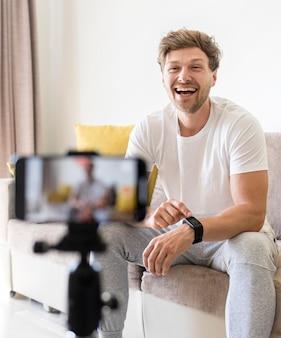 Portrait d'un homme positif enregistrant pour un blog personnel