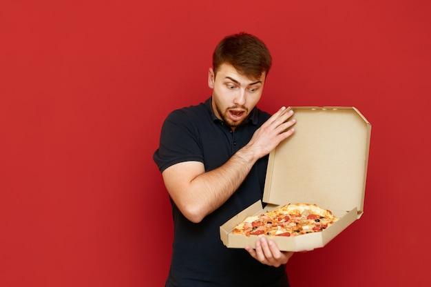 Portrait d'homme positif se dresse et ouvre la boîte de délicieuses pizzas fraîches