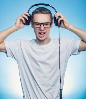 Portrait d'un homme qui criait heureux écouter de la musique dans les écouteurs et les a retirés de la tête sur fond bleu.
