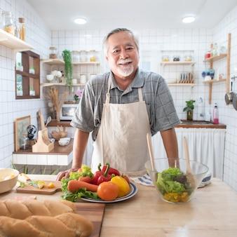 Portrait d'un homme qui cuisine dans la cuisine.