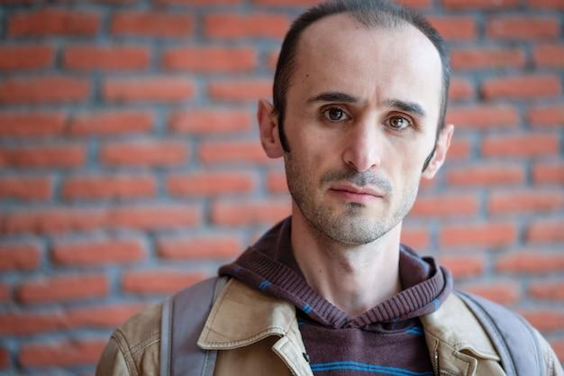 Portrait d'un homme de race blanche avec une barbe et des cheveux courts avec une veste en cuir marron