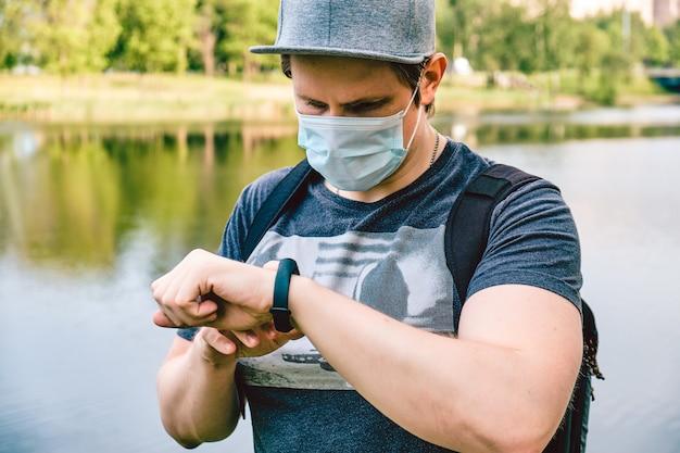 Portrait d'un homme de race blanche dans un masque médical lors d'une pandémie dans la ville utilise une montre intelligente. nouveau normal.