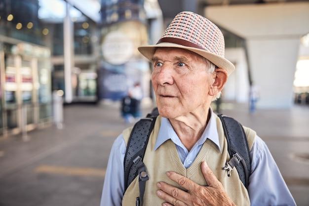 Portrait d'un homme de race blanche effrayé avec un sac à dos debout seul dans la rue