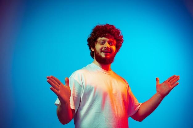 Portrait de l'homme de race blanche isolé sur fond bleu studio en néon