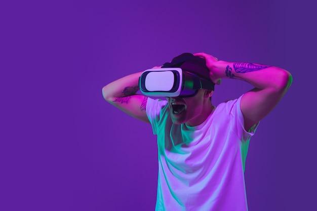 Portrait de l'homme de race blanche isolé sur fond de studio violet en néon