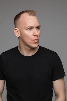 Portrait d'homme de race blanche en t-shirt noir regarde vers la gauche