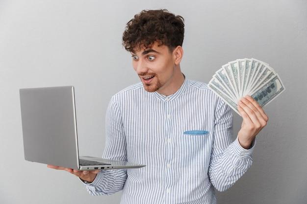 Portrait d'un homme ravi vêtu d'une chemise tout en tenant un ordinateur portable en argent et un tas d'argent en espèces isolé sur un mur gris