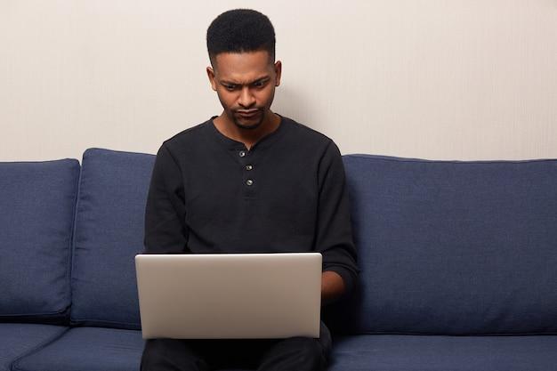 Portrait d'un homme réfléchi assidu assis sur un canapé bleu, ayant un ordinateur portable sur les jambes, à l'aide de son appareil, travaillant comme pigiste