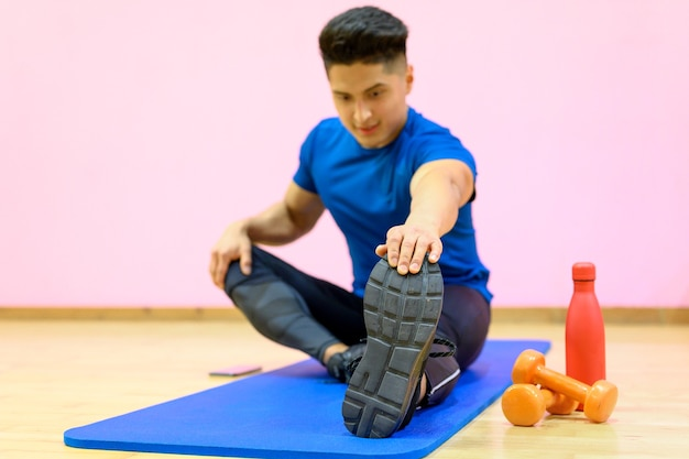 Portrait d'un homme de remise en forme faisant des exercices d'étirement au gymnase