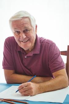 Portrait d'un homme retraité souriant écrit sur du papier blanc