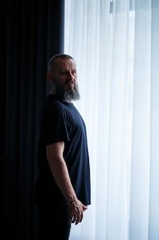 Portrait d'un homme réussi adulte aux cheveux gris avec un visage sérieux dans un t-shirt noir