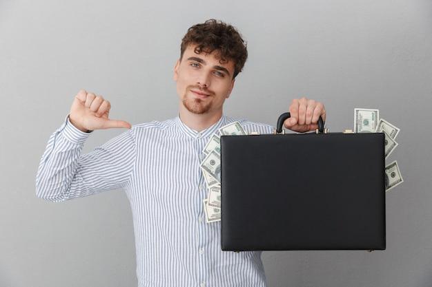 Portrait d'un homme réussi vêtu d'une chemise pointant tout en tenant un diplomate avec un tas d'argent en espèces isolé sur un mur gris
