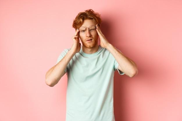 Portrait d'un homme rousse à lunettes tordues touchant la tête et se sentant étourdi ou nauséeux, ayant la gueule de bois ou des maux de tête, debout sur fond rose.