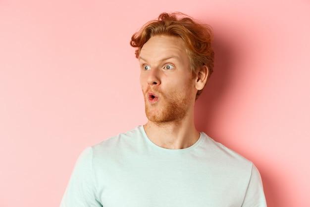 Portrait d'un homme roux surpris avec une barbe, regardant à gauche et disant wow, levant les sourcils étonnés, debout sur fond rose.