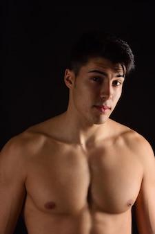 Portrait d'un homme sans vêtements fond noir