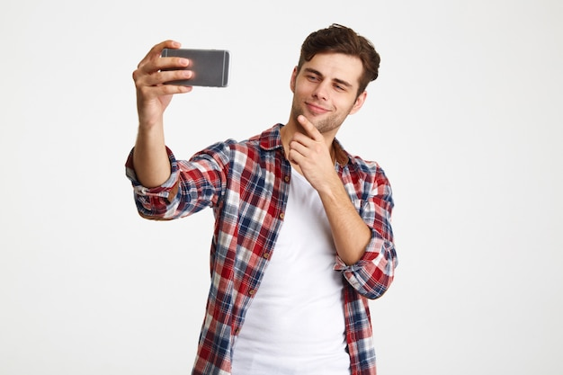 Portrait d'un homme satisfait prenant un selfie en position debout