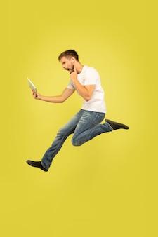 Portrait d'homme sautant heureux sur mur jaune