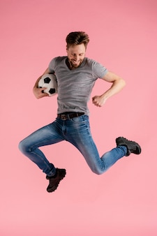 Portrait homme sautant tenant un ballon de football