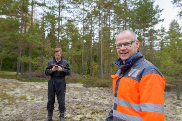 Portrait d'homme scandinave mature et jeune homme scandinave prêt pour la récolte dans la forêt ensemble à l'extérieur