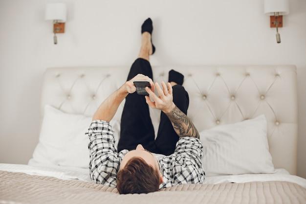 Portrait d'homme se détendre à la maison avec smartphone