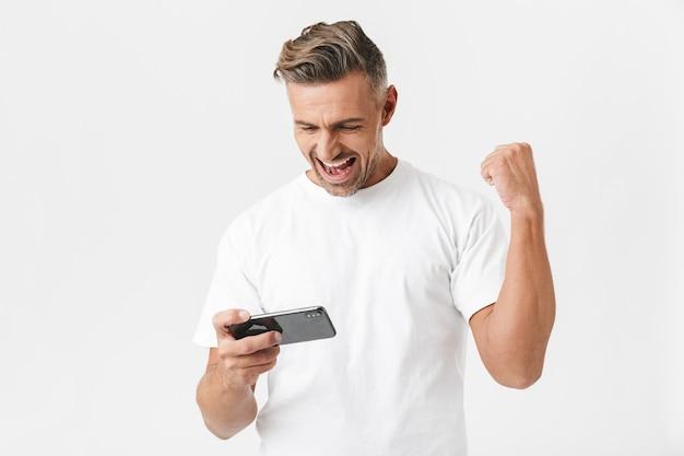 Portrait d'un homme séduisant des années 30 portant un t-shirt décontracté utilisant un smartphone et jouant à des jeux vidéo isolés sur blanc