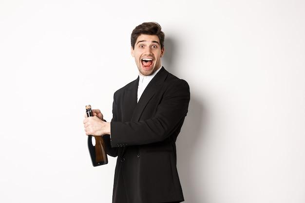 Portrait d'un homme séduisant en costume noir, faisant un clin d'œil à la caméra et ouvrant une bouteille de champagne, célébrant le nouvel an, debout sur fond blanc.