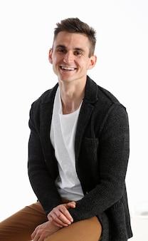 Portrait d'un homme séduisant dans un pull et un t-shirt, assis sur une chaise et souriant