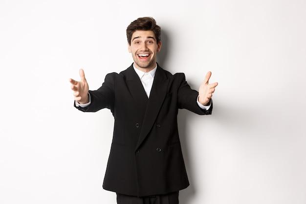 Portrait d'un homme séduisant et heureux en costume, organisant une fête, tendant les mains vers l'avant pour vous saluer, veut tenir quelque chose ou embrasser, debout sur fond blanc.