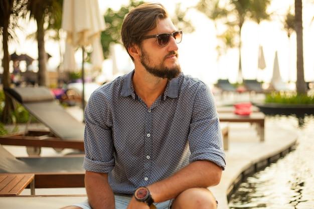 Portrait d'un homme séduisant avec des lunettes de soleil en plein air