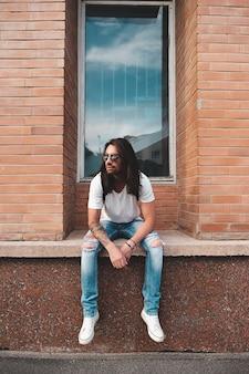 Portrait homme séduisant près de fenêtre sur scène urbaine