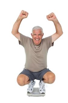 Portrait d'un homme senior acclamant l'échelle de poids