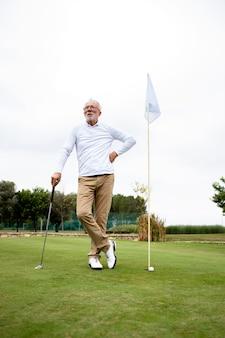 Portrait d'un homme senior actif jouant au golf sur le terrain de golf et profitant du temps libre à l'extérieur.