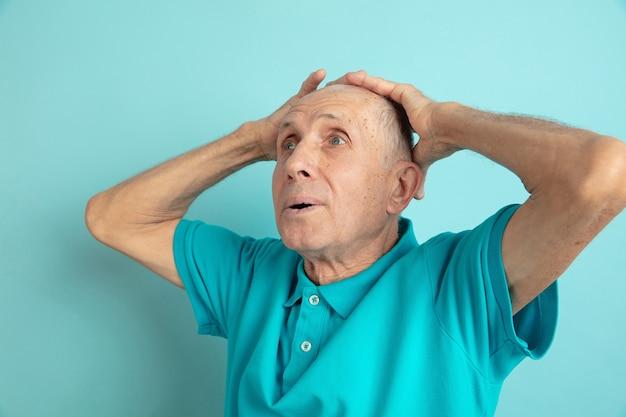 Portrait de l'homme senior caucasien isolé sur mur bleu